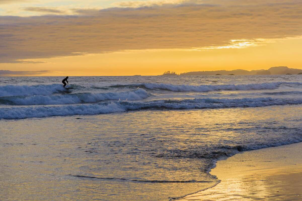Surfer at sunset, Long Beach, Pacific Rim National Park, Vancouver Island, British Columbia.