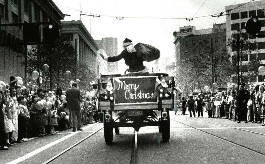 The Emporium's Santa Claus rides down Market Street during a holiday parade. Photo: Fred Larson / Fred Larson / The Chronicle 1982 / ONLINE_YES