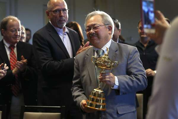 Marry Ed Lee carries the Ryder Cup to the stage after PGA of America officials announce that the Olympic Club will host the 2028 PGA Championship and the Ryder Cup in 2032, in San Francisco, Calif. on Wednesday, Nov. 8, 2017.