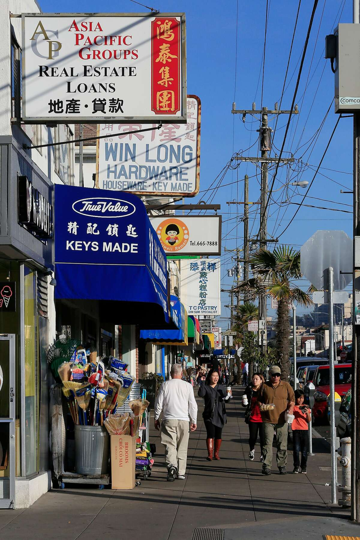 People walk along Irving Street below store signs on Thursday, December 14, 2017 in San Francisco, Calif.