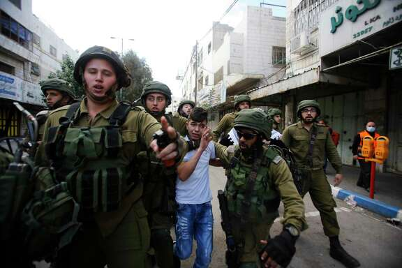 Israeli soldiers detain a Palestinian boy during clashes Friday at a protest in Hebron against U.S. President Donald Trump's decision to recognize Jerusalem as the capital of Israel.
