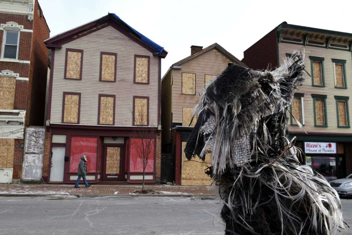 Fire damaged buildings are boarded up Remsen St. across from a melted fiberglass lamppost on Friday, Dec. 15, 2017, in Cohoes, N.Y. (Will Waldron/Times Union)