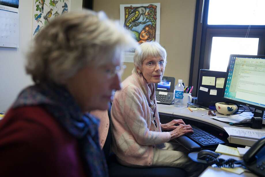 Barbara Toschi (right), who has been processing applications for Season of Sharing emergency grants as a volunteer for more than two decades, chats with fellow volunteer Mary Kreider at their office. Photo: Peter DaSilva, Special To The Chronicle