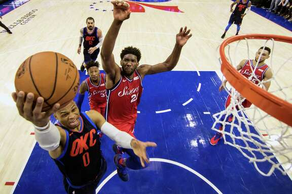 Oklahoma City's Russell Westbrook, left, goes up for two of his 27 points as Philadelphia's Joel Embiid, right, defends during the second overtime period.