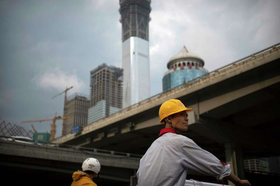"""FILE - In this Aug. 16, 2017, file photo, a construction worker waits to cross an intersection near buildings under construction in the central business district of Beijing. The World Inequality Report 2018 released Friday, Dec. 15, 2017, is based on a massive collection of data compiled by an international team of researchers. It shows inequality has soared since 1980 although the global top """"1 percent"""" saw their share of global income shrink slightly after the global financial crisis. The share of global income going to the bottom 50 percent rose slightly, to just under 10 percent, thanks to gains in populous, fast-growing China and India. (AP Photo/Mark Schiefelbein, File) Photo: Mark Schiefelbein, STF / Copyright 2017 The Associated Press. All rights reserved."""
