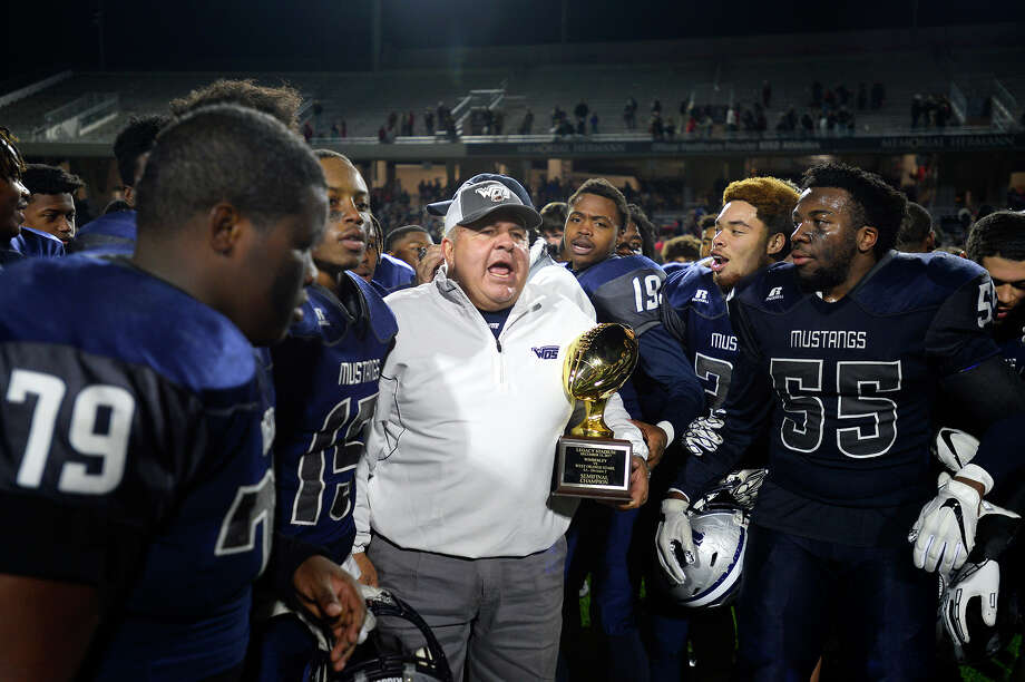West Orange-Stark players crowd around head coach Cornel Thompson as he holds the trophy after they beat Wimberley in the Class 4A Division 2 state semifinal game at Legacy Stadium in Katy on Friday night.  Photo taken Friday 12/15/17 Ryan Pelham/The Enterprise Photo: Ryan Pelham / ©2017 The Beaumont Enterprise/Ryan Pelham