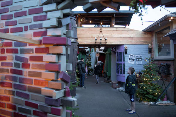 Visitors flock to the now-famed recreation of Diagon Alley, a shopping street location from the Harry Potter books, at a home in Ballard is turned Christmas-themed, seen on Thursday, Dec. 13, 2017.