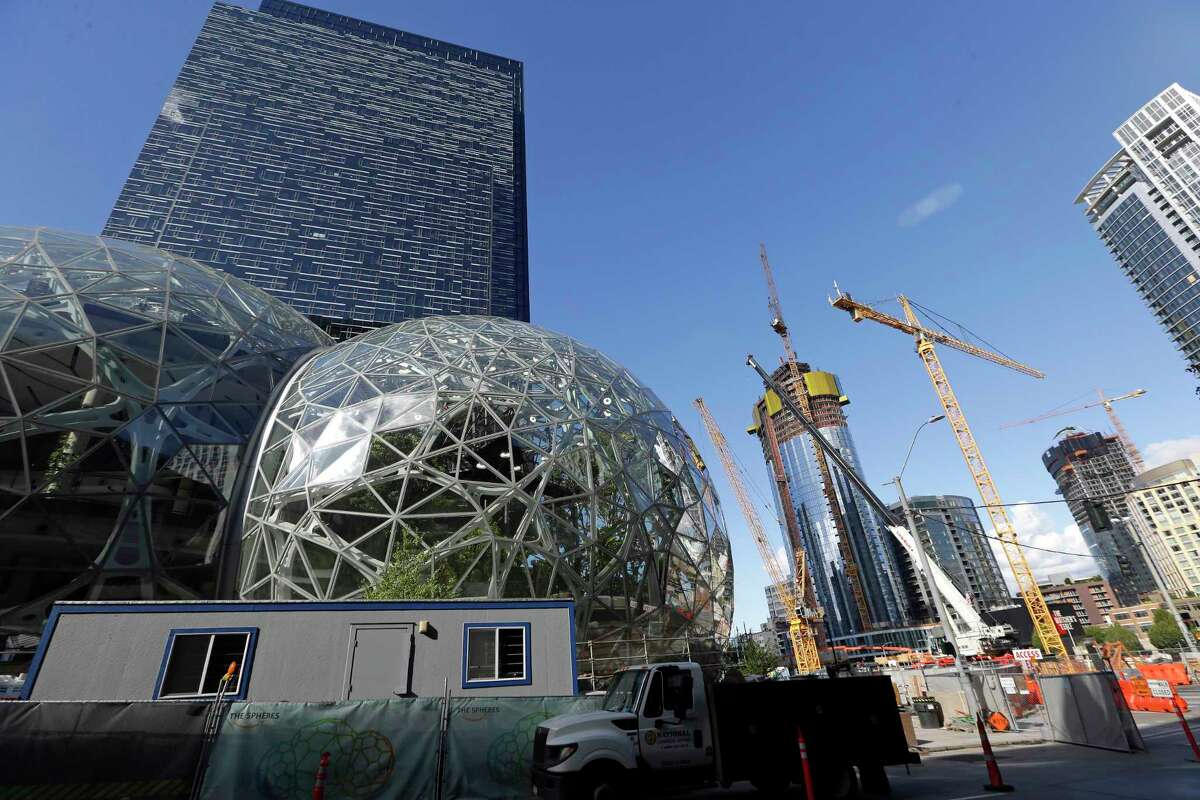 Large spheres take shape in front of an Amazon building, behind, as construction continues across the street. Seattle is among the cities that have flourished since the Great Recession officially began in December 2007. But many U.S. areas have managed only modest recoveries.