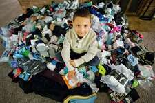 Jaxson Lewis, 6, poses for a photo next to the pile of 1,428 pairs of socks he and his family collected and donated to Midland's Open Door and the Salvation Army. (Katy Kildee/kkildee@mdn.net)