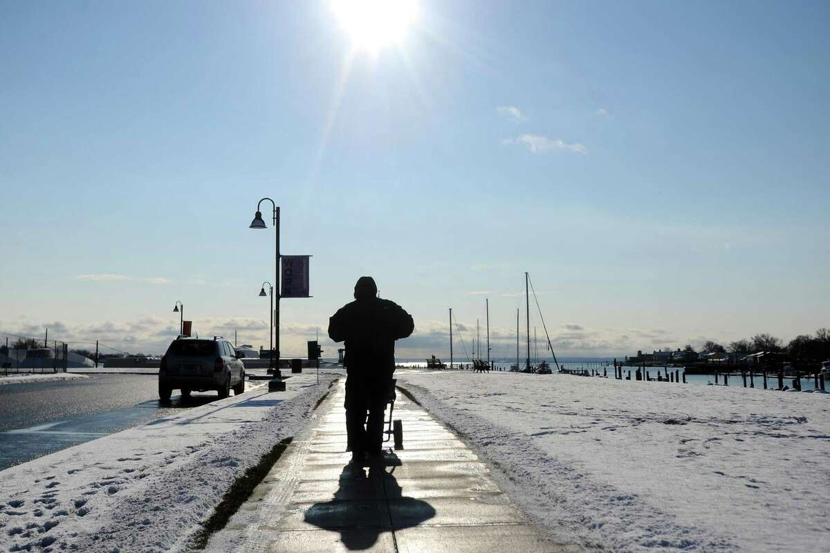 A man pushes a salt spreader down Pacific Street after the overnight snow in the Harbor Point area of Stamford, Conn. on Thursday, Dec. 14, 2017.