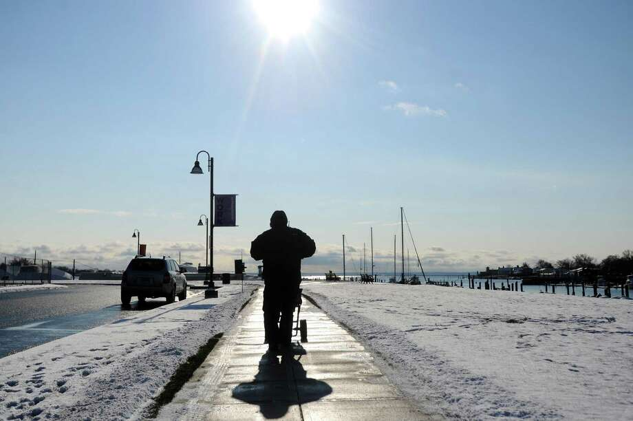 A man pushes a salt spreader down Pacific Street after the overnight snow in the Harbor Point area of Stamford, Conn. on Thursday, Dec. 14, 2017. Photo: Michael Cummo / Hearst Connecticut Media / Stamford Advocate