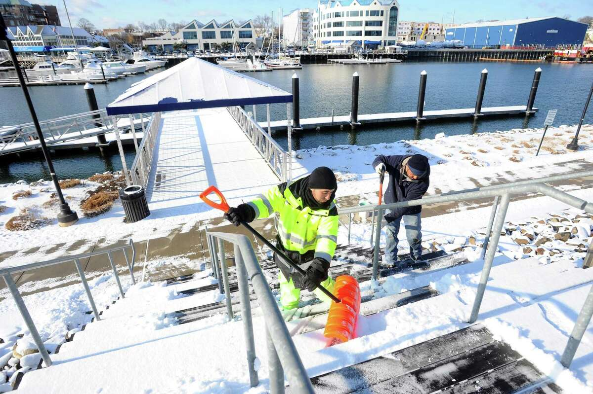 A crew shovels the snow off the steps on Pacific Street after the overnight snow in the Harbor Point area of Stamford, Conn. on Thursday, Dec. 14, 2017.