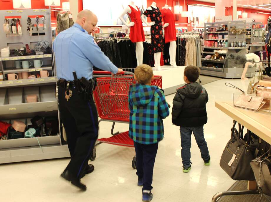 Officer Rick Thompson (left), of the EPD, shopped with area children Saturday morning at the Edwardsville Target for the department's annual Christmas with a Cop event. Photo: Cody King • Cking@edwpub.net