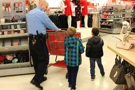 Officer Rick Thompson (left), of the EPD, shopped with area children Saturday morning at the Edwardsville Target for the department's annual Christmas with a Cop event.