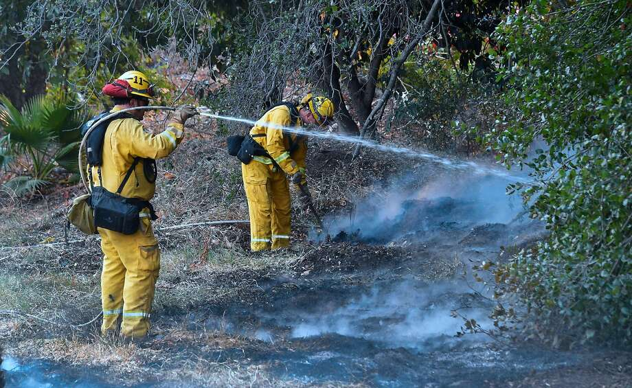 Firefighters water down burning embers in Fillmore (Ventura County) on Friday as the Thomas Fire flared up. Photo: FREDERIC J. BROWN, AFP/Getty Images