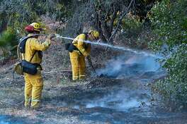 Firefighters water down burning embers from an overnight fire in Fillmore, California on December 15, 2017, as the Thomas Fire flared up again, growing to 252,500 acres and becoming the fourth largest fire in California's history.   The Thomas Fire has blackened over 250,000 acres (100,000 hectares) since it broke out ten days ago, Cal Fire said, making it the fourth-largest blaze in the state's history. / AFP PHOTO / FREDERIC J. BROWNFREDERIC J. BROWN/AFP/Getty Images
