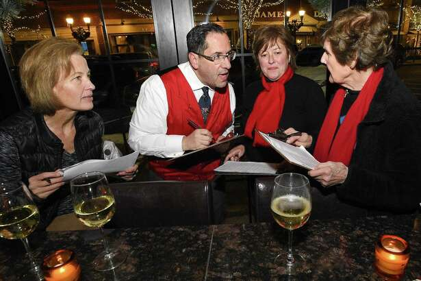From left, Judges Joanne Parsons of Trumbull, Frank Gaffney of Norwalk, Meg Finnerod of Old Greenwich and Marion Glowka of Stamford have a group discussion as they tally up their scores following a walking tour to review the entries in the eighth annual Holiday Window Salute in Stamford (Conn.) Downtown on Dec. 14, 2017.