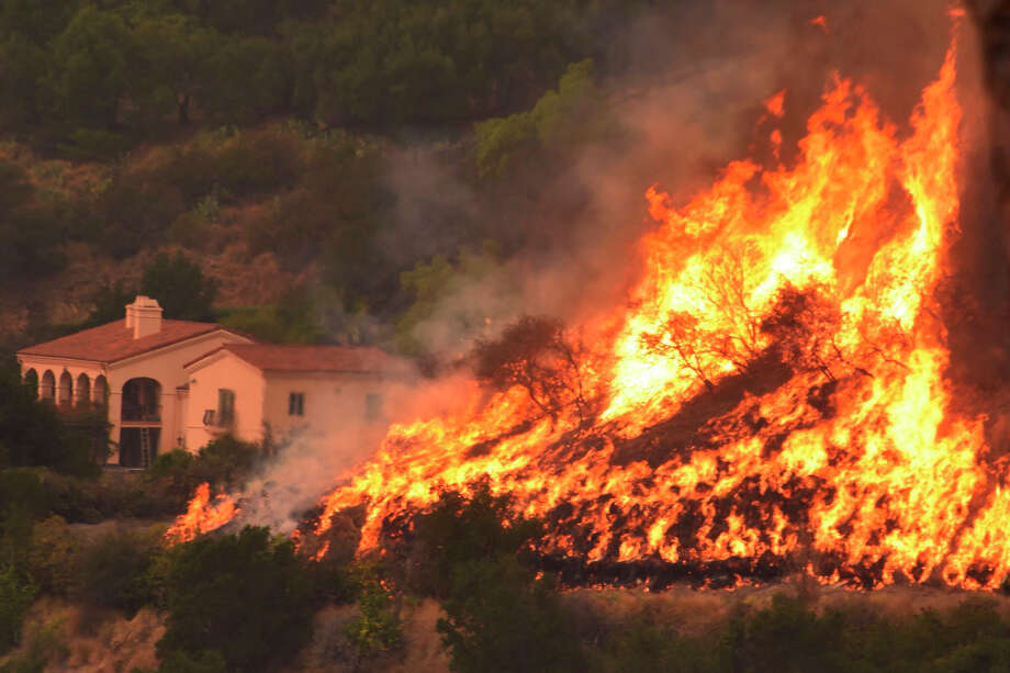 In this Thursday, Dec. 14, 2017, photo provided by the Santa Barbara County Fire Department, flames from a back firing operation underway rise behind a home off Ladera Lane near Bella Vista Drive in Santa Barbara, Calif. Red Flag warnings for the critical combination of low humidity and strong winds expired for a swath of Southern California at midmorning but a new warning was scheduled to go into effect Saturday in the fire area due to the predicted return of winds. The so-called Thomas Fire, the fourth-largest in California history, was 35 percent contained after sweeping across more than 394 square miles (1,020 sq. kilometers) of Ventura and Santa Barbara counties since it erupted Dec. 4 a few miles from Thomas Aquinas College. (Mike Eliason/Santa Barbara County Fire Department via AP) Photo: Mike Eliason, AP / Santa Barbara County Fire Department