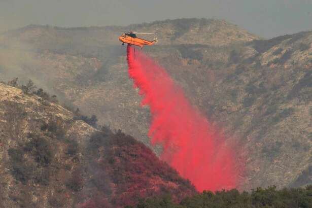 In this photo provided by the Santa Barbara County Fire Department, a helicopter drops fire retardant onto a hillside Friday, Dec. 15, 2017,  in San Ysidro Canyon in Montecito, Calif. Red Flag warnings for the critical combination of low humidity and strong winds expired for a swath of Southern California at midmorning but a new warning was scheduled to go into effect Saturday in the fire area due to the predicted return of winds. The so-called Thomas Fire, the fourth-largest in California history, was 35 percent contained after sweeping across more than 394 square miles (1,020 sq. kilometers) of Ventura and Santa Barbara counties since it erupted Dec. 4 a few miles from Thomas Aquinas College. (Mike Eliason/Santa Barbara County Fire Department via AP)