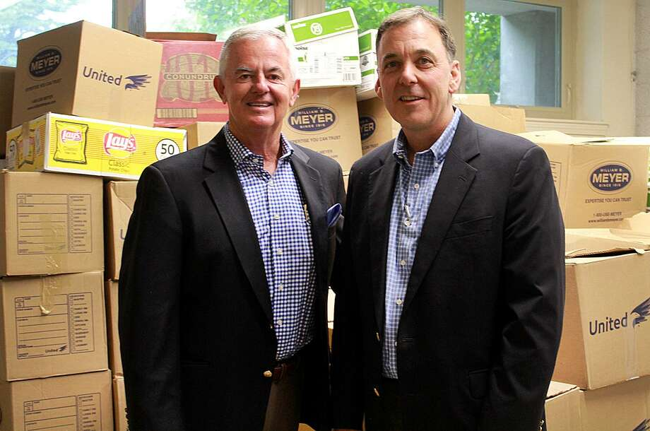 Kevin Kelleher, CEO of Cartus, and Bob Gallucci, vice president of sales for William B. Meyer, pose by the boxes of food that Cartus employees collected to benefit Move for Hunger. Photo: Chris Bosak / Hearst Connecticut Media / The News-Times