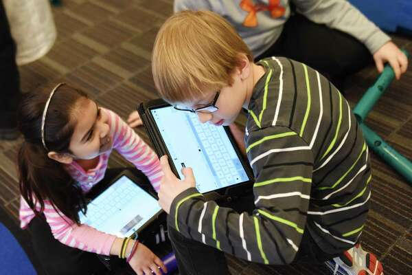 Fourth-graders Dina Quevedo and Max Smith use iPads to learn about boom sticks in music class at Hamilton Avenue School in Greenwich, Conn. Tuesday, March 31, 2015.  With the advances of technology in the classroom, students and teachers are balancing digital learning on platforms like the iPad with traditional pen and paper, non-digital resources.
