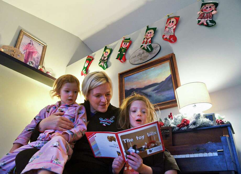 Becca Riding helps read a short story to her daughters Maggie, 3, left, and Lucy, 5, before school at their home in American Fork, Utah. Photo: Isaac Hale Photo For The Washington Post / Isaac Hale