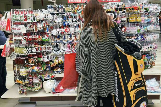 Nancy Colagiacomo of Montreal shops for ornaments at a kiosk in Crossgates Mall on Black Friday Nov. 24, 2017 in Guilderland, N.Y. She was able to find a Steelers golf bag for her husband. (Lori Van Buren / Times Union)
