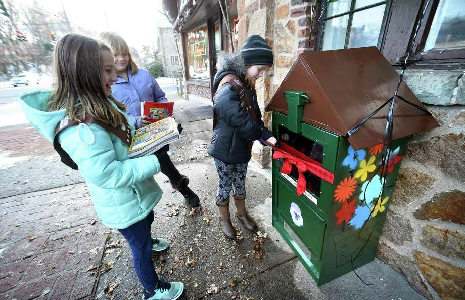 Left to right, Girl Scouts Troop 60651 Brownies Charlotte Trama, 8, and Aubrey Powers, 9, watch Ellie Solomon, 8, cut a ribbon on a New Haven Register vending machine transformed into a LIttle Free Library at 1630 Whitney Ave. in Hamden on Saturday. Photo: Arnold Gold / Hearst Connecticut Media / New Haven Register