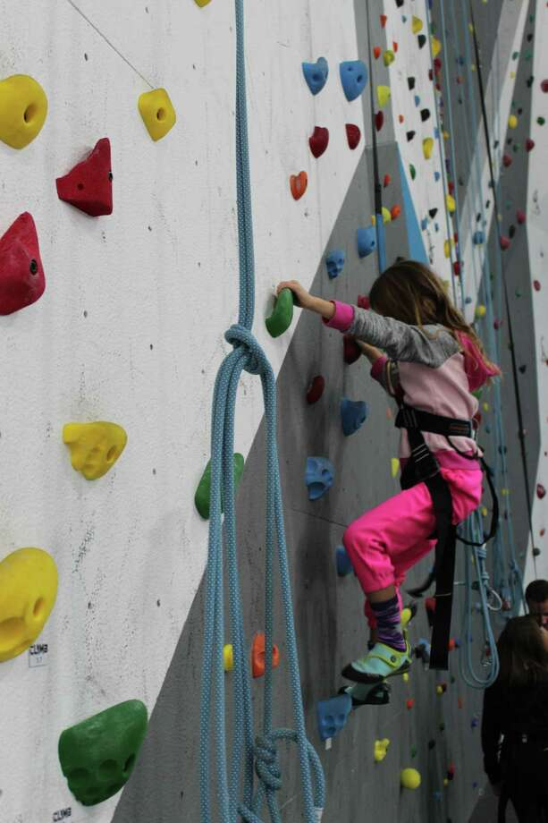 Jessy Jordy, 7, climbs a rock wall for the first time during the grand opening celebration at Climb Woodlands, a newly opened gym located at 7515 Oak Bluff Drive, Suite C, Magnolia. Photo: Patricia Dillon