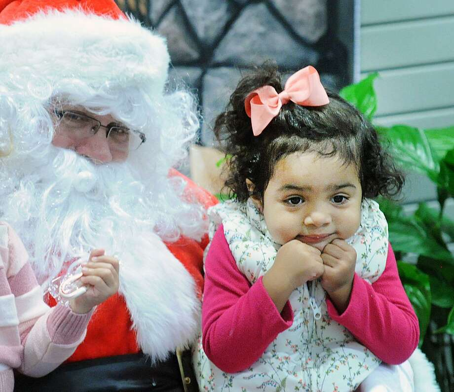 Anabella Correa, 2, of Greenwich, appeared to get slightly bored while having her photo taken with Santa during the Holiday Family Fun event at the YWCA of Greenwich, Conn., Saturday, Dec. 16, 2017. Photo: Bob Luckey Jr. / Hearst Connecticut Media / Greenwich Time