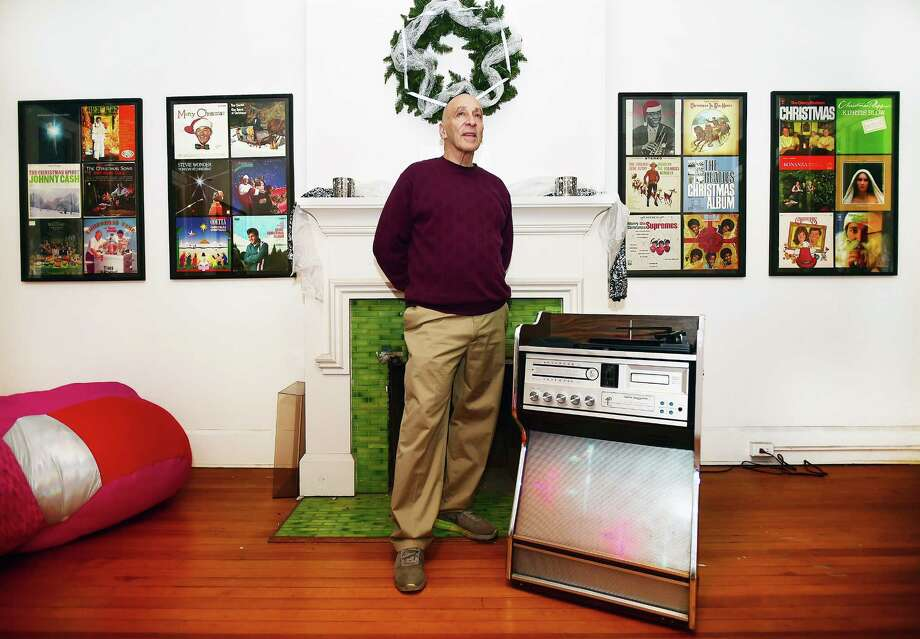 Sam Goldenberg plays an album on his 1970's Morse Electrophonic Jukebox, surrounded by his collection of Christmas music on exhibit at the John Slade Ely House at 51 Trumbull St. in New Haven. Photo: Catherine Avalone / Hearst Connecticut Media / New Haven Register