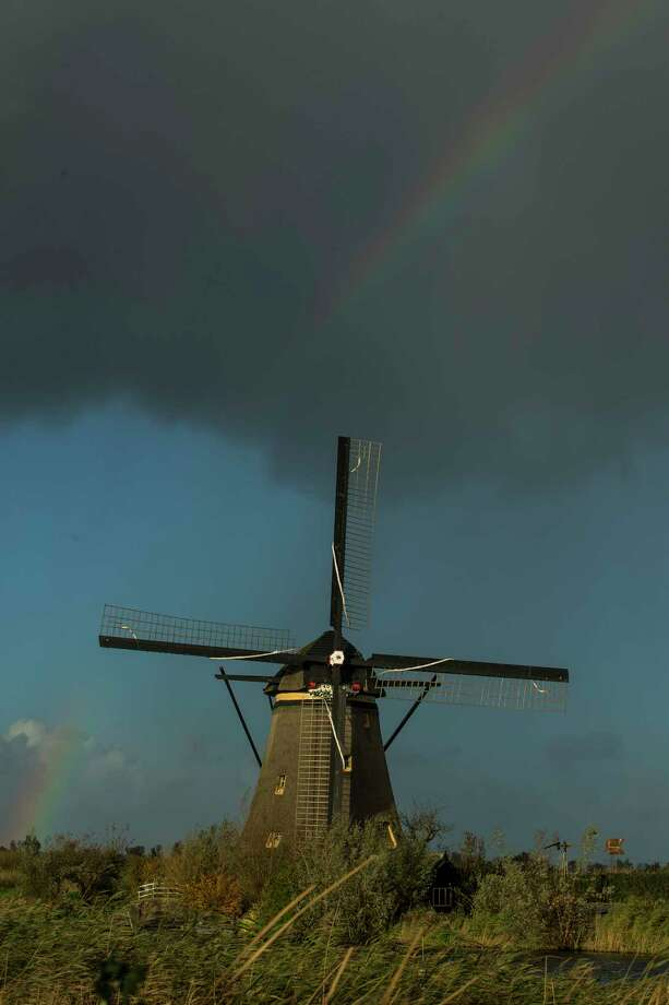 A rainbow appears over one of the windmills at Kinderdijk. The windmills pump water out of the area that sits below sea level.  Photo: Michael Ciaglo, Houston Chronicle / Michael Ciaglo