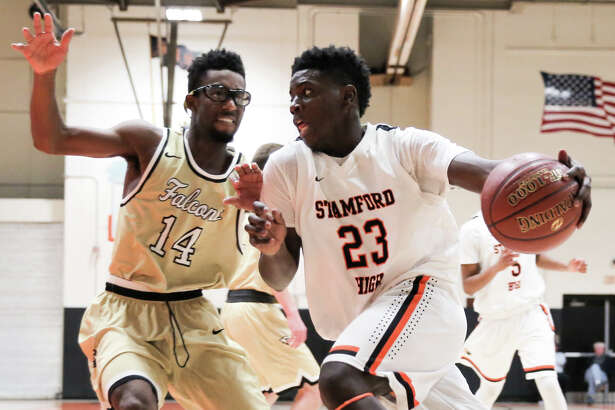Tevin St. John takes the ball past Nate Aime during Stamford's victory over Joel Barlow at Stamford High School on Saturday, December 16, 2017.