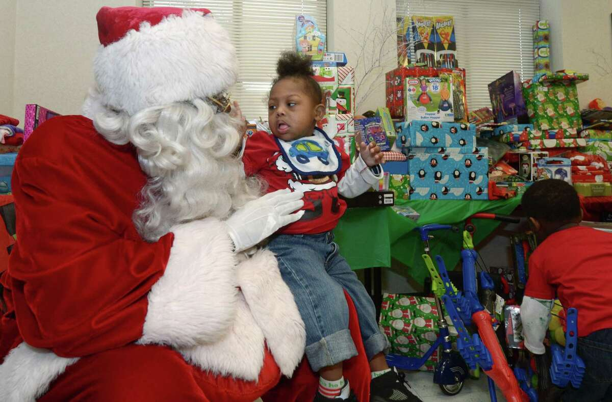 Santa Claus portrayed by James Dupree greets Kaleb Broodie, 3, as the DDH Hope Foundation Inc. holds their second annual Fund A Family event for families or children in need of Christmas celebratory items Saturday, December 16, 2017, in the Norwalk Police Department Community Room in Norwalk, Conn.