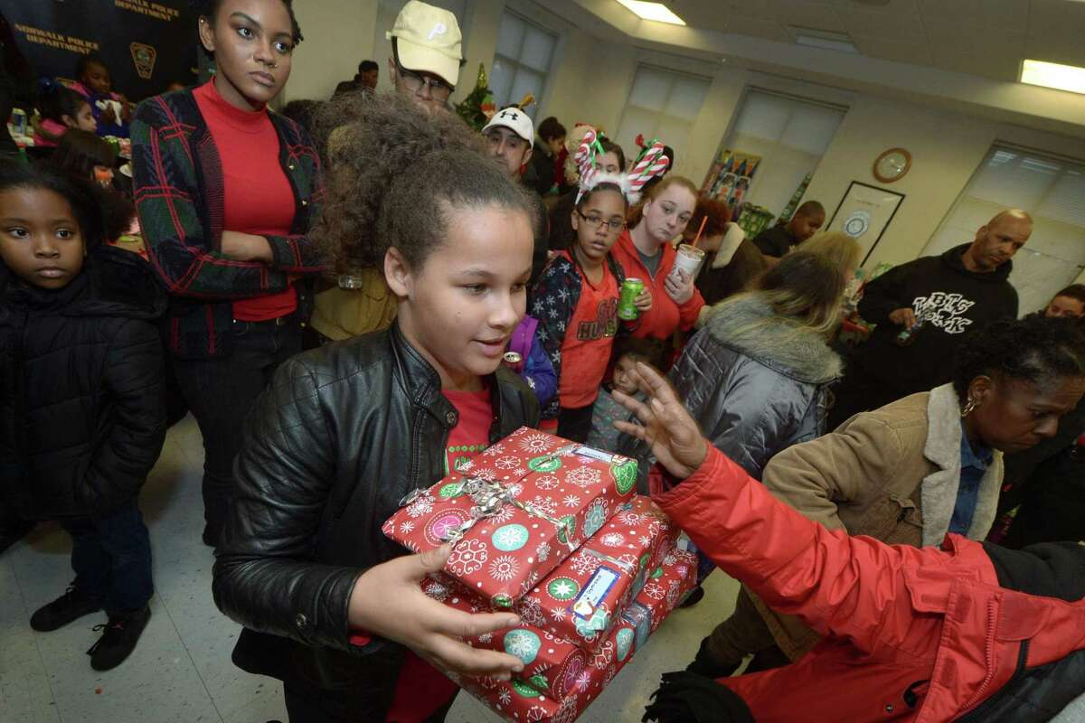 Diamond Fuller, 8, receives her gifts as the DDH Hope Foundation Inc. holds their second annual Fund A Family event for families or children in need of Christmas celebratory items Saturday, December 16, 2017, in the Norwalk Police Department Community Room in Norwalk, Conn.