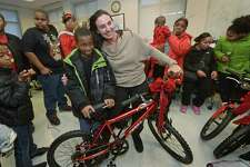 Kyrese Addison, 7, receives a bike from Jen Padovani as the DDH Hope Foundation Inc. holds their second annual Fund A Family  event for families or children in need of Christmas celebratory items Saturday, December 16, 2017, in the Norwalk Police Deptartment Community Room in Norwalk, Conn.
