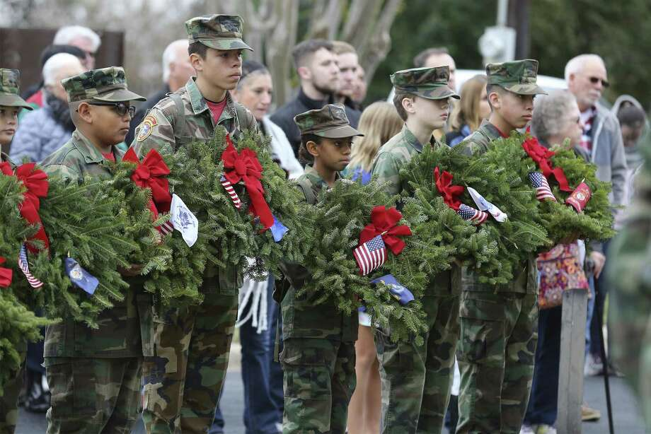 Members of San Antonio Young Marines hold wreaths to honor the branches of the military as they, along with volunteers, gather at San Antonio National Cemetery to take part in Wreaths Across America on Saturday. The same ceremony was held at Fort Sam Houston National Cemetery on Saturday. Photo: Kin Man Hui /San Antonio Express-News / ©2017 San Antonio Express-News