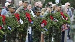 Members of San Antonio Young Marines hold wreaths to honor the branches of the military as they, along with volunteers, gather at San Antonio National Cemetery to take part in Wreaths Across America on Saturday. The same ceremony was held at Fort Sam Houston National Cemetery on Saturday.