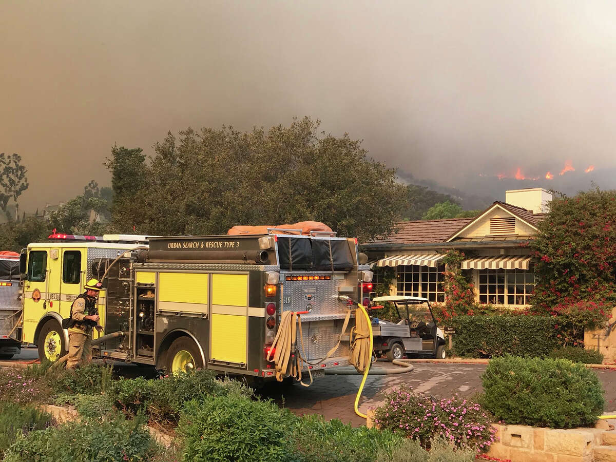 Fire fighters work to protect the historic San Ysidro Ranch in Montecito, Calif., Saturday. The fire, which began Dec. 4, has burned more than 700 homes and forced about 95,000 people to evacuate.