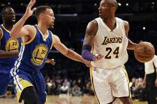 Los Angeles Lakers forward Kobe Bryant, right, handles the ball while Golden State Warriors guard Stephen Curry, left, defends during the first half of an NBA basketball game in Los Angeles, Sunday, March 6, 2016. (AP Photo/Kelvin Kuo)