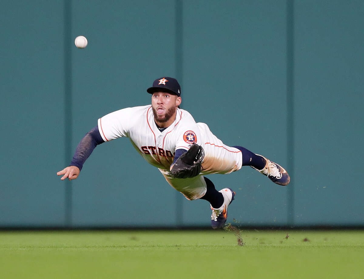 Houston Astros center fielder George Springer (4) dives in an attempt to catch Washington Nationals Michael Taylor's double in the fifth inning of an MLB game at Minute Maid Park, Tuesday, Aug. 22, 2017, in Houston.