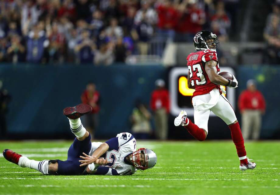 New England Patriots quarterback Tom Brady left, falls to the field as Atlanta Falcons cornerback Robert Alford runs the ball for a touchdown after a pick six during the second quarter of Super Bowl LI at NRG Stadium on Sunday, February 5, 2017. Photo: Karen Warren/Houston Chronicle