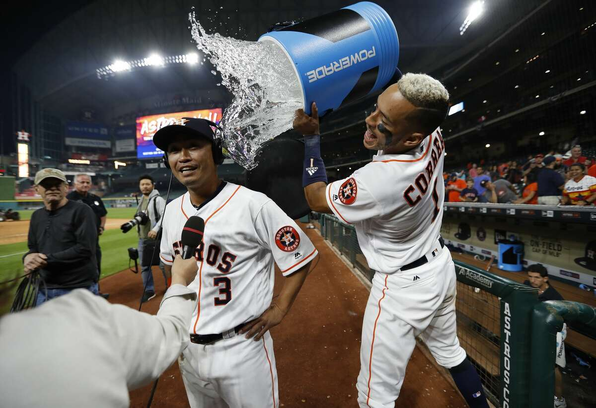 Houston Astros shortstop Carlos Correa (1) dumps water on Norichika Aoki (3) after Aoki's clutch single set up George Springer's home run in the thirteenth inning of an MLB baseball game at Minute Maid Park, Wednesday, April 5, 2017, in Houston.