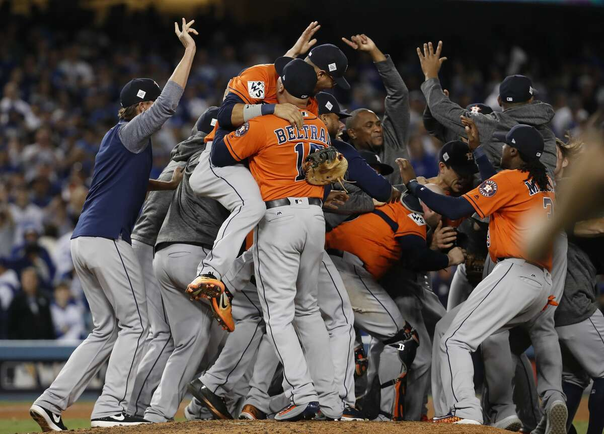 Houston Astros Carlos Beltran (15) celebrates with teammates mobbing pitcher Charlie Morton after Game 7 of the World Series at Dodger Stadium on Wednesday, Nov. 1, 2017, in Los Angeles.