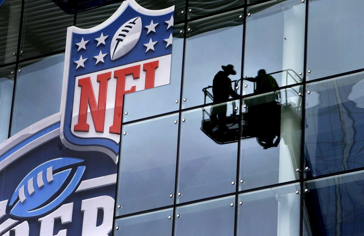 Yari Rodrigues, left, and Osvaldo Gonzalez with Sign Systems Inc. are shown in a reflection as they apply a vinyl graphic sign to the outside of the George R. Brown Convention Center Tuesday, Jan. 10, 2017, in Houston. The sign is for the NFL Experience, a Super Bowl LI event that features NFL themed games and activities. It will be open on January 28-29 and February 1-5.
