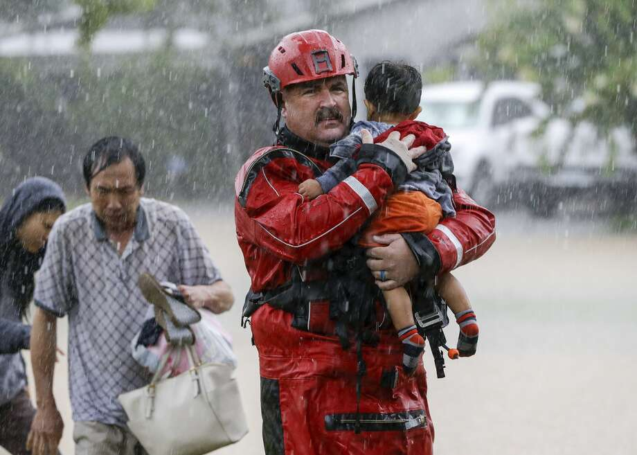 Chad Smith, a Task Force One member from the Dallas Fire Dept., carries Christian Rodriguez, 1, from a rescue boat as people are transferred to a pickup point along Edgebrook Sunday, August 27, 2017 in Houston. Much of the area was flooded ing the aftermath of Hurricane Harvey. Photo: Melissa Phillip