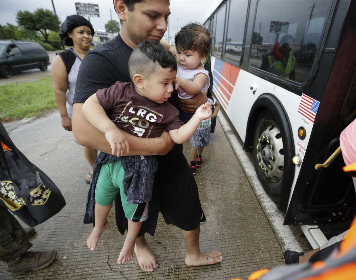 A man carries two children as they board a Metro bus on Interstate 45 to be taken to a shelter at the George R. Brown Convention Center on Aug. 27, 2017. Keep clicking to see dramatic rescues made during Hurricane Harvey.