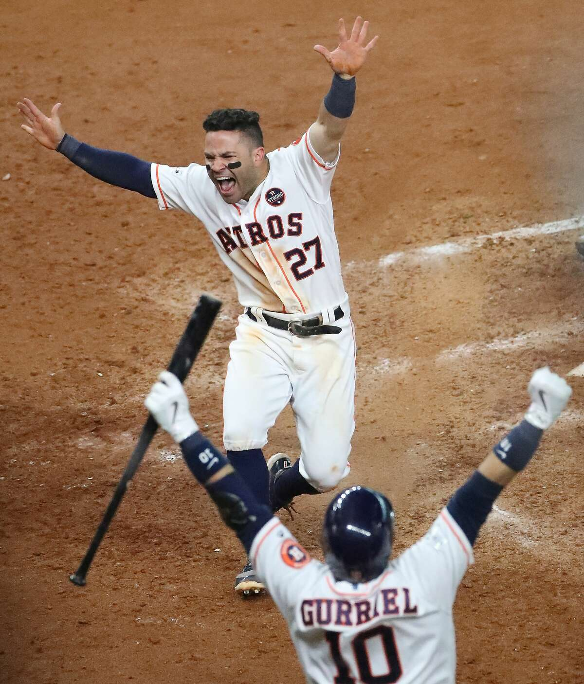 Houston Astros second baseman Jose Altuve (27) scores the winning run after Houston Astros shortstop Carlos Correa (1) hit him in to win the ALCS Game 2 Saturday, Oct. 14, 2017, in Houston.