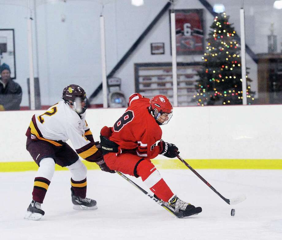 Alexander Mozian of Greenwich, right, prepares to shoot while being defended by Dareios Linss of St. Joseph's during the high school ice hockey game between Greenwich High School and St. Joseph High School at Hamill Rink in Greenwich on Saturday night. The Cardinals won 10-2. Photo: Bob Luckey Jr. / Hearst Connecticut Media / Greenwich Time