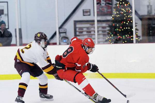 Alexander Mozian of Greenwich, right, prepares to shoot while being defended by Dareios Linss of St. Joseph's during the high school ice hockey game between Greenwich High School and St. Joseph High School at Hamill Rink in Greenwich on Saturday night. The Cardinals won 10-2.